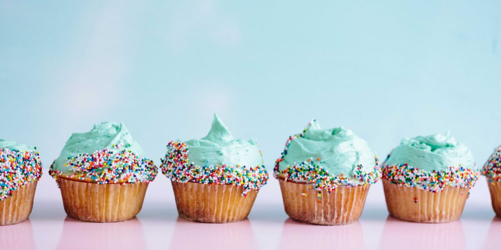row of cupcakes with blue buttercream