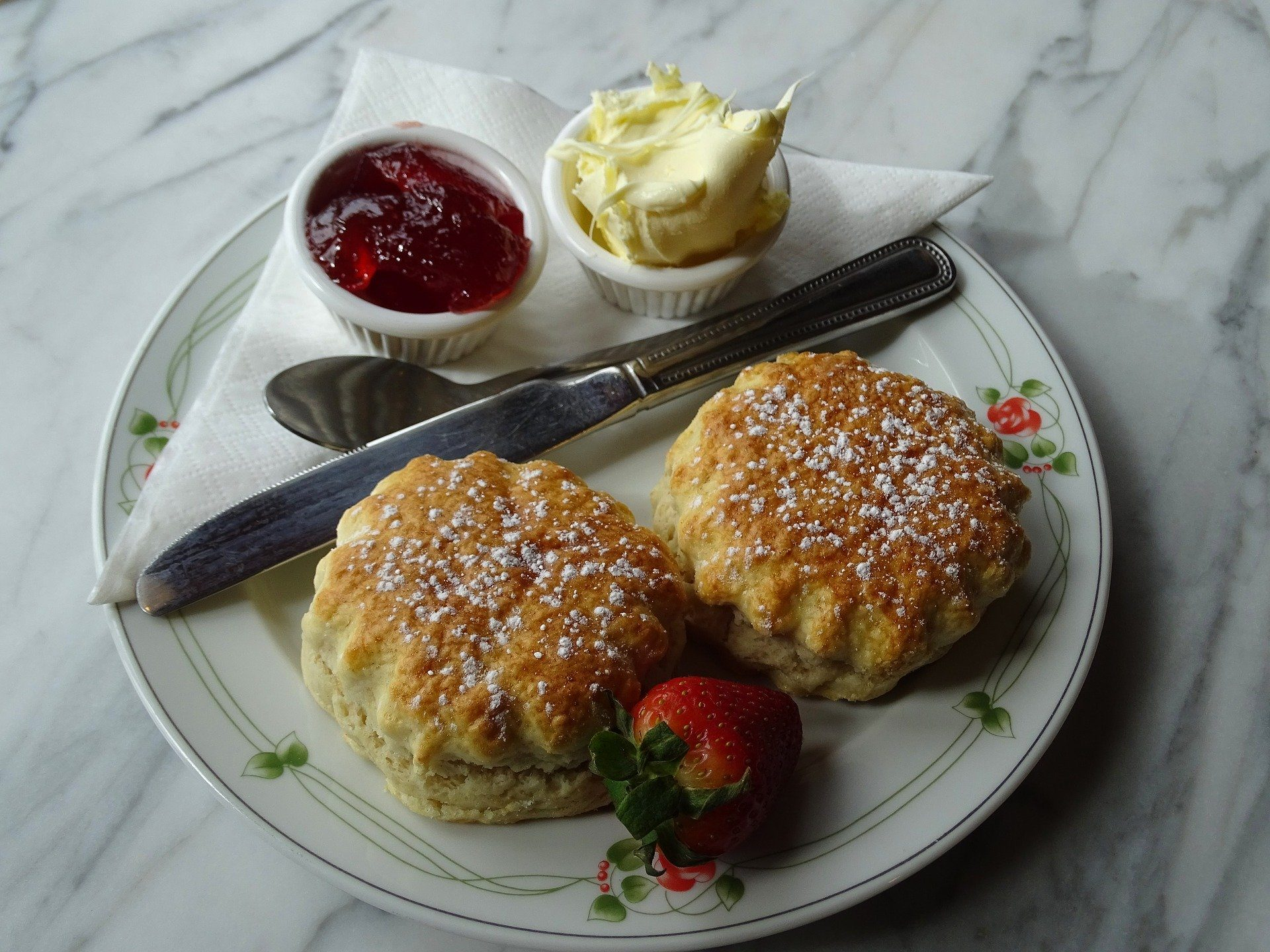 image shows a plate with 2 plain scones, a pot of clotted cream and a pot of jam